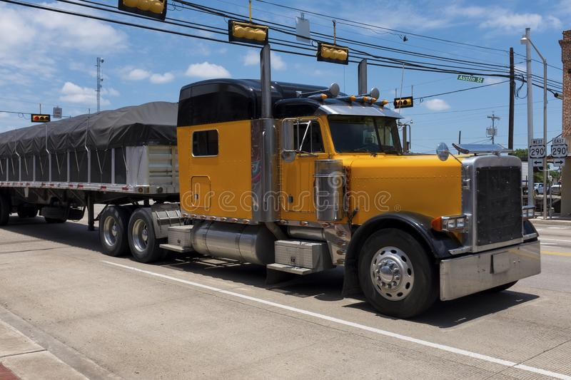 Yellow truck in a highway crossing a small american town royalty free stock photos
