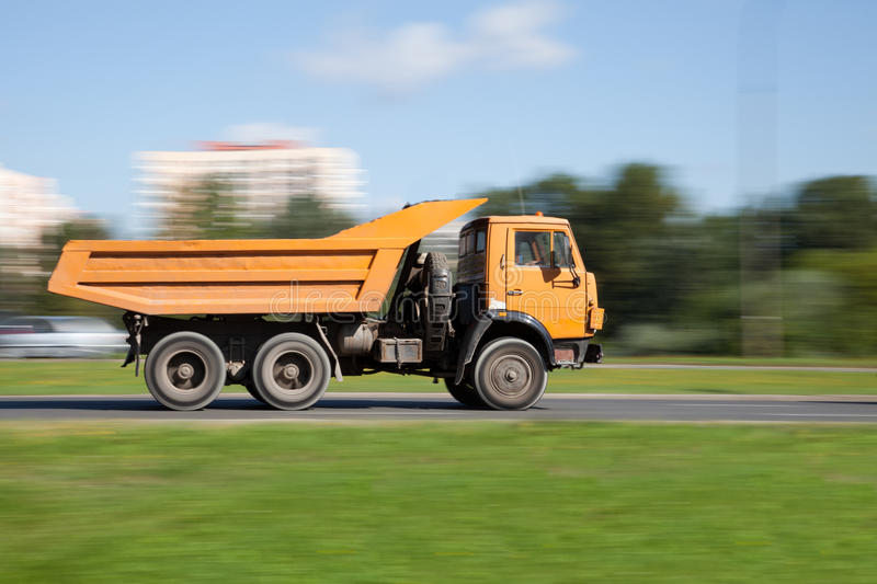 Yellow truck in motion blur. Panning image of yellow truck in intentional motion blur stock images