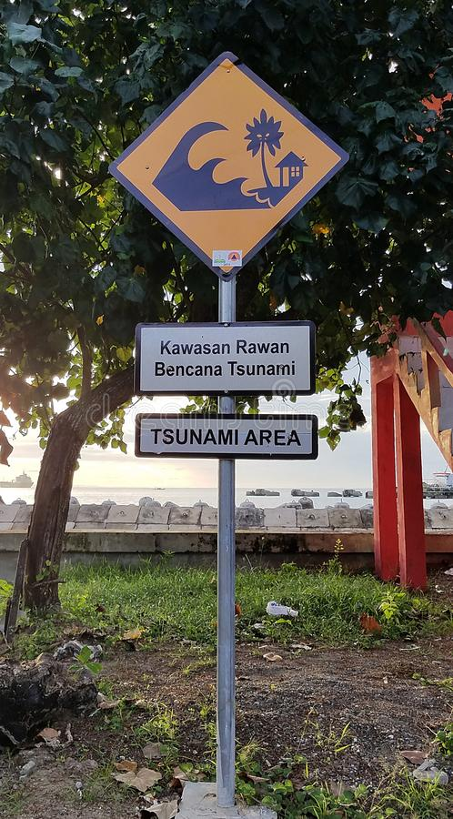 Yellow Tsunami Hazard Zone Sign. Yellow tsunami hazard zone warning sign posted along the beaches and coastline of Meulaboh, Aceh Barat, Indonesia with in royalty free stock images