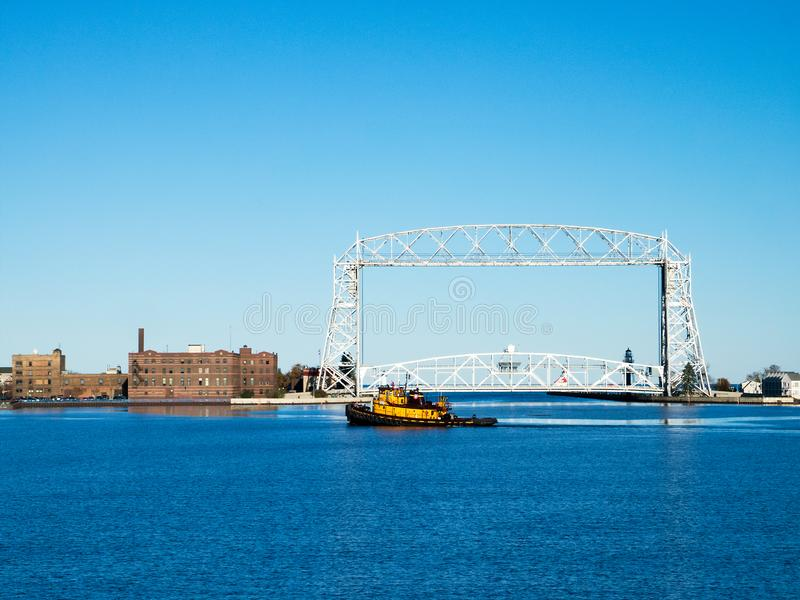 Yellow Tug Boat sails near Duluth Minnesota aerial lift bridge in late afternoon. On sunny day stock photography