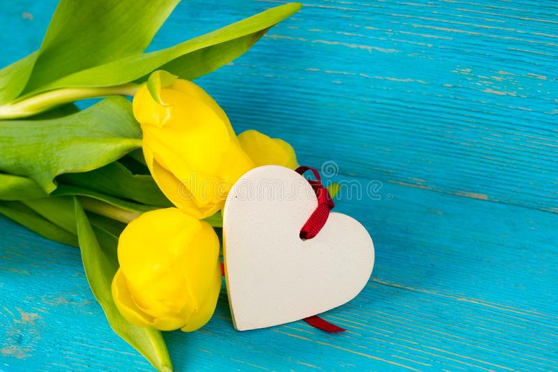 Yellow tulips bouquet with heart shape on turquoise wooden background stock image