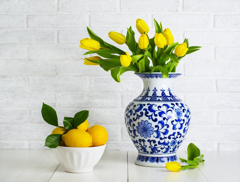 Yellow tulips in the chinese vase. And lemons in the bowl stock image