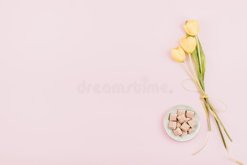 Yellow tulips flowers and pink chocolate on pastel background. Festive birthday flat lay. Greeting for Womens or Mothers Day. Gift, box, table, woman, present stock images