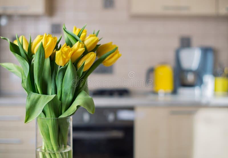 Yellow tulips on kitchen background royalty free stock photo