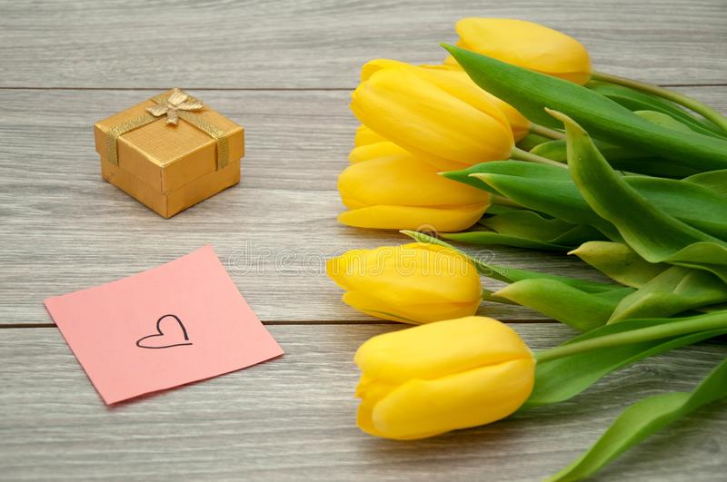 Yellow tulips lie on a gray wooden table next to a sticker on which a heart is drawn. Flowers with a note and a gift for the beloved royalty free stock photography