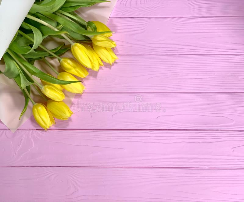 Yellow tulips lie on a pink background. A wooden background with a place for text. Bouquets of flowers in packaging for the holiday stock image