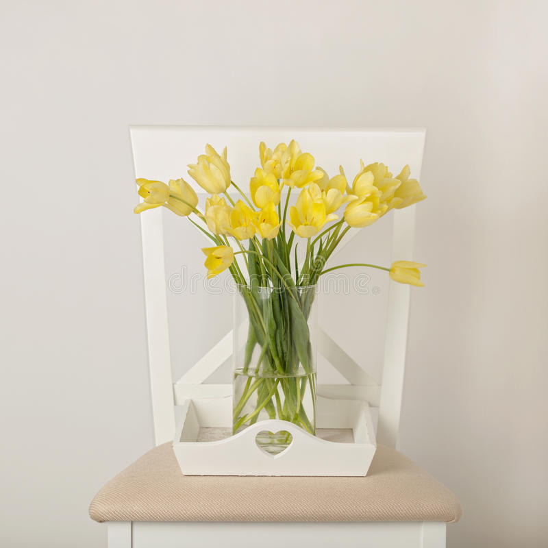Yellow tulips in vase on white tray on the chair. royalty free stock image
