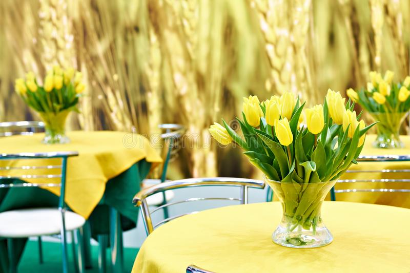 Yellow tulips on tables in interior stock photos