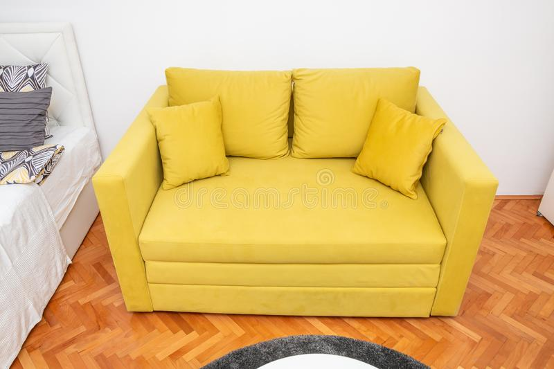 Yellow two-seat sofa. Modern yellow two-seat sofa with pillows in hotel room. Close up stock photos