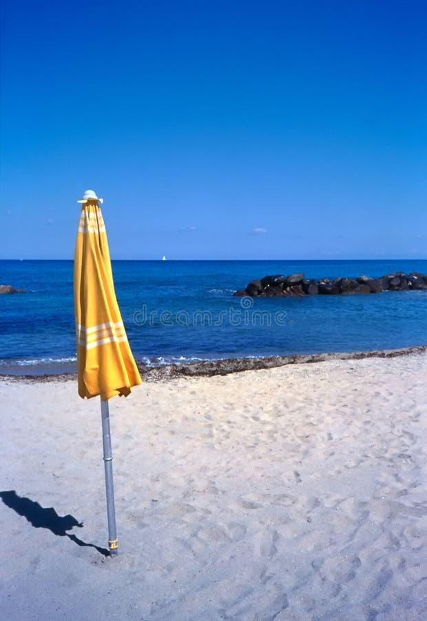 Yellow umbrella on a beach stock photos
