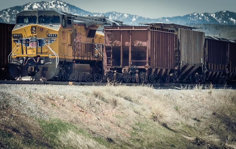 A Yellow Union Pacific Diesel Locomotive Engine And Grain Hopper Cars royalty free stock photography