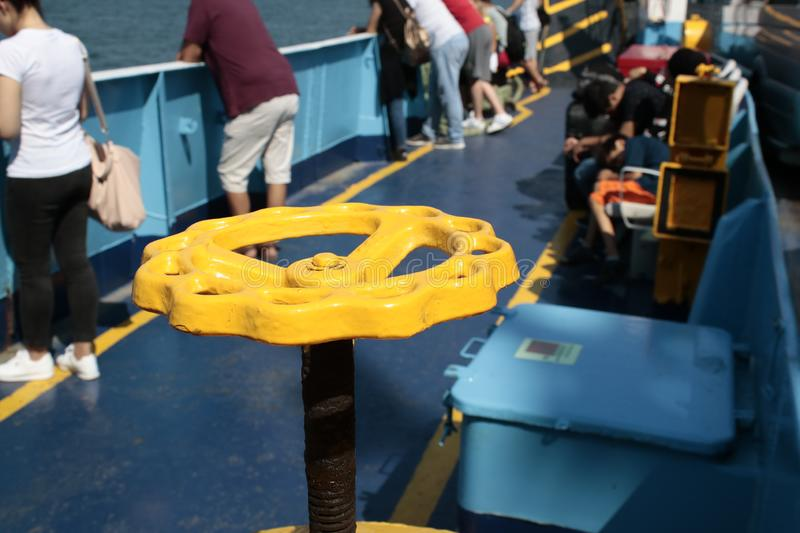 Yellow valve in ship and people sitting and watching the sea in background. Photographed on the steamer stock images