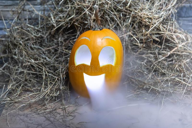 Yellow and very funny happy pumpkin for halloween celebration with smoke or vapor from the mouth. With lighting Stands on a wooden. Stand against a stone wall stock images