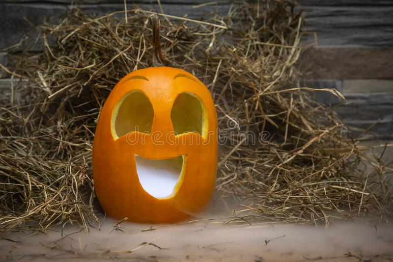 Yellow and very funny happy pumpkin for halloween celebration with smoke or vapor from the mouth. Stands on a wooden stand against. A stone wall stock images