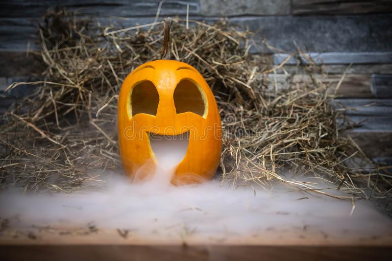 Yellow and very funny happy pumpkin for halloween celebration with smoke or vapor from the mouth. Stands on a wooden stand against. A stone wall royalty free stock photo