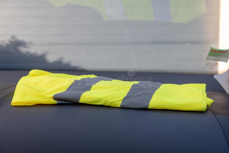 Yellow vest on a dashboard. Car in protest against tax increases in France royalty free stock image