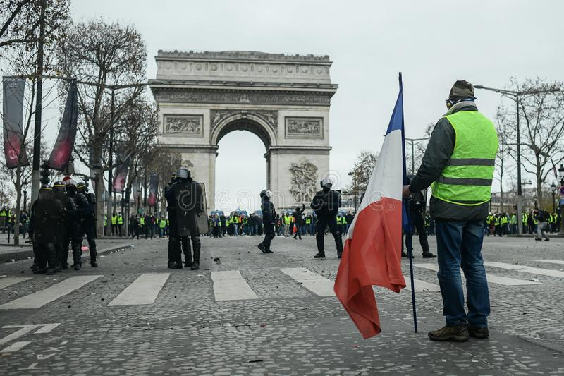 Yellow vests - Gilets jaunes protests - Protester holding a french flag stands in front of riot police. Paris, France - 8 December 2018: a protester holding a royalty free stock photography