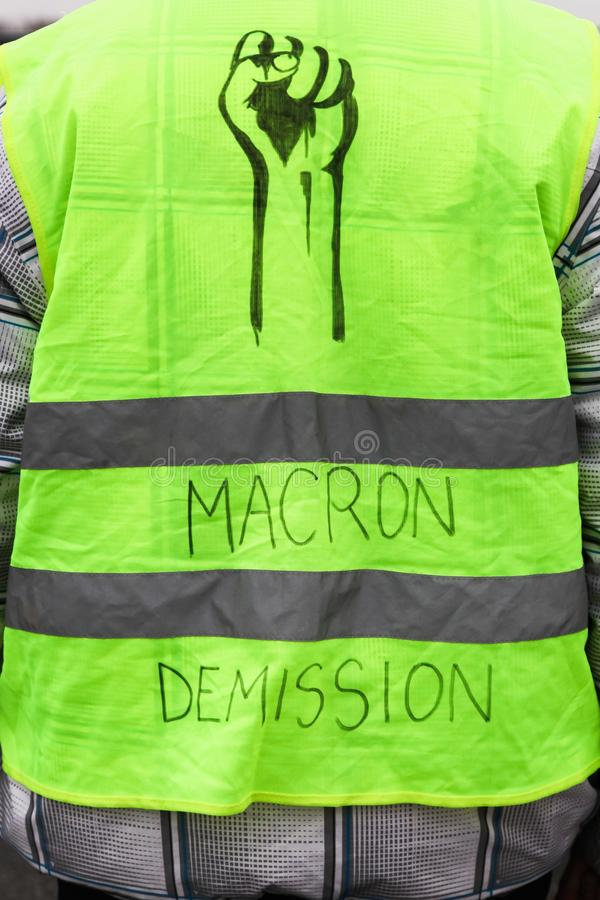 Yellow vests protest against higher fuel prices in France. And text on the yellow vest president Macron departure in French royalty free stock image