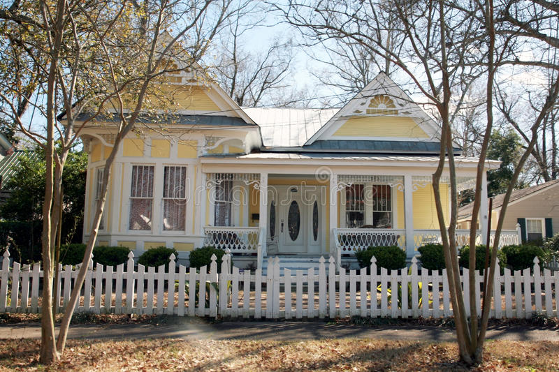 Yellow Victorian Style Home. Yellow one-story Victorian style home with a white picket fence stock photos