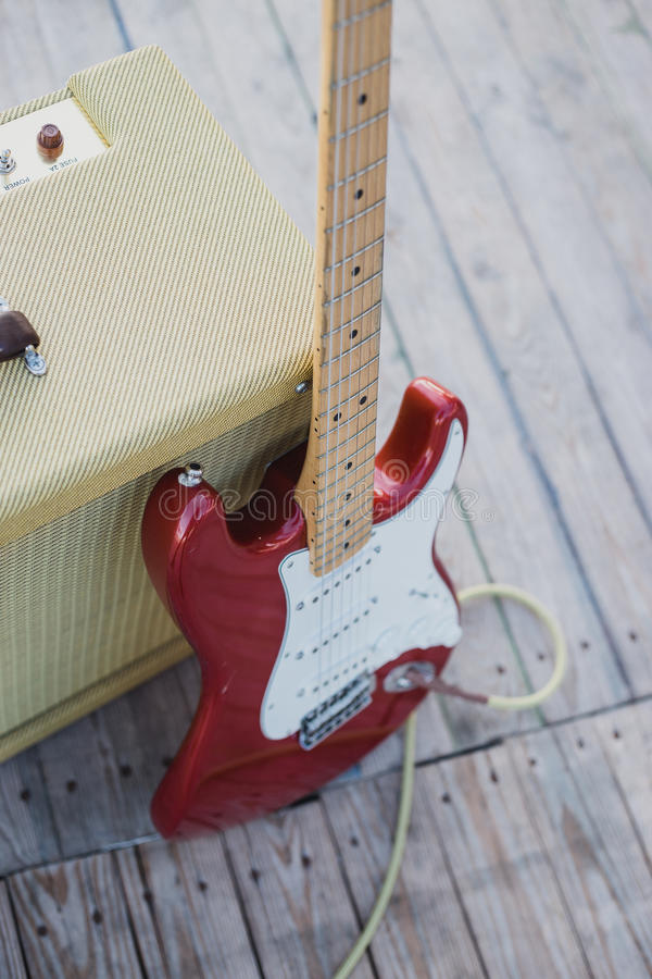 Yellow vintage guitar aplifier with cable and red electric guitar stock images