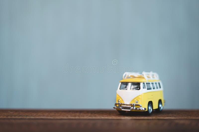 Yellow vintage miniature minivan on a wooden table. royalty free stock photo