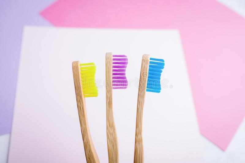 Yellow, violet and blue bamboo toothbrushes. Eco-friendly concept. Minimal, colored geometric background. Copy space stock image