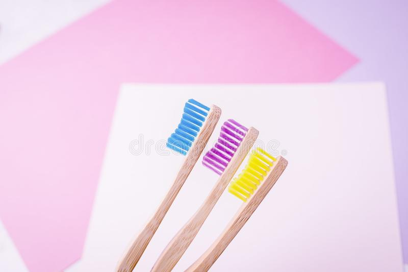 Yellow, violet and blue bamboo toothbrushes. Eco-friendly concept. Minimal, colored geometric background. Copy space royalty free stock photos