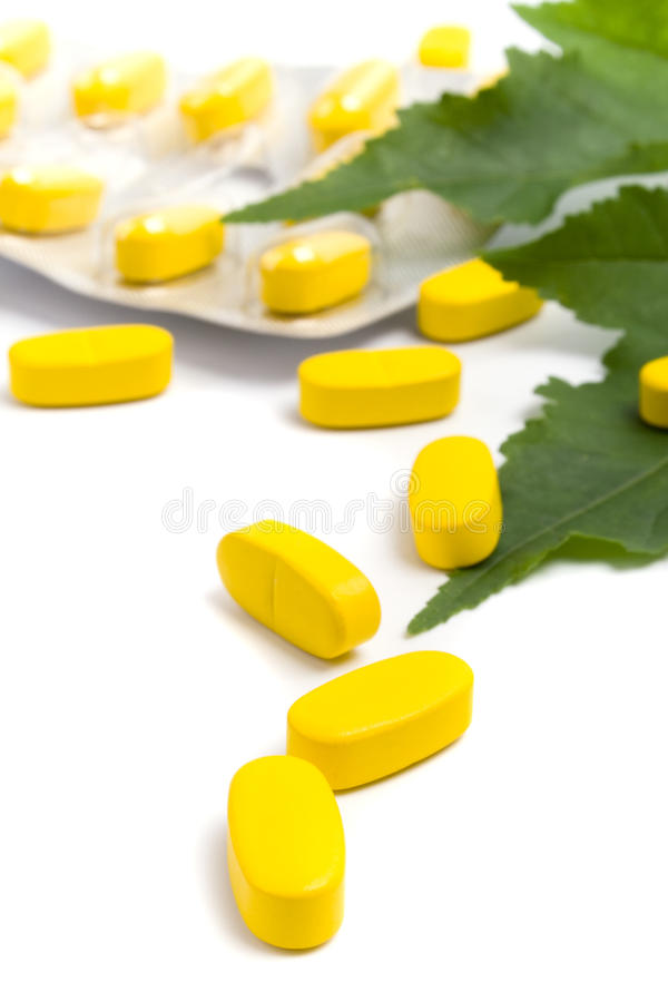 Yellow Vitamin Pills And Green Leaves Royalty Free Stock Images