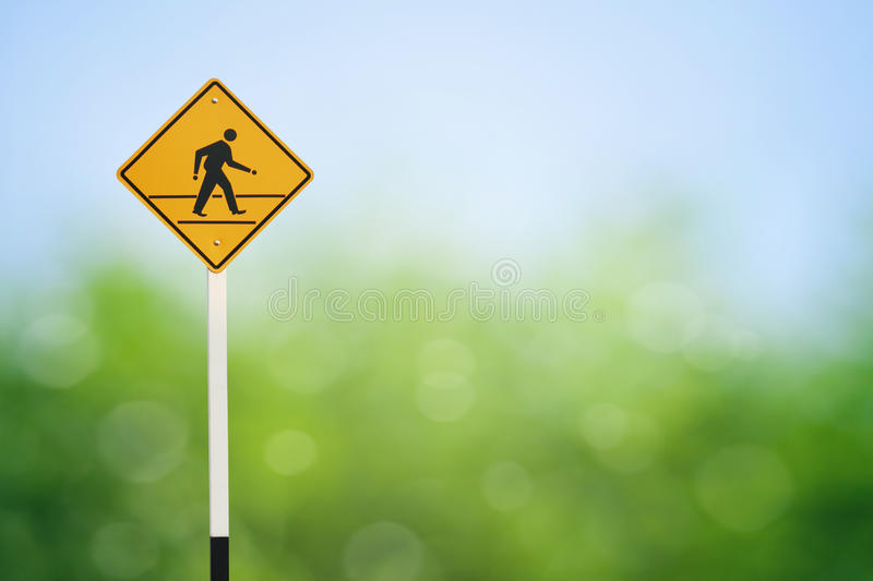 Yellow walk sign. On green background stock photos