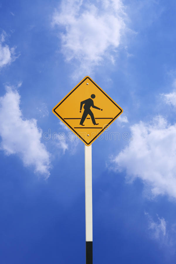 Yellow walk sign. With blue sky royalty free stock image