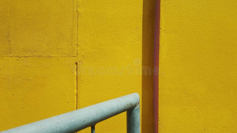 The yellow wall and the grey pipe. royalty free stock images
