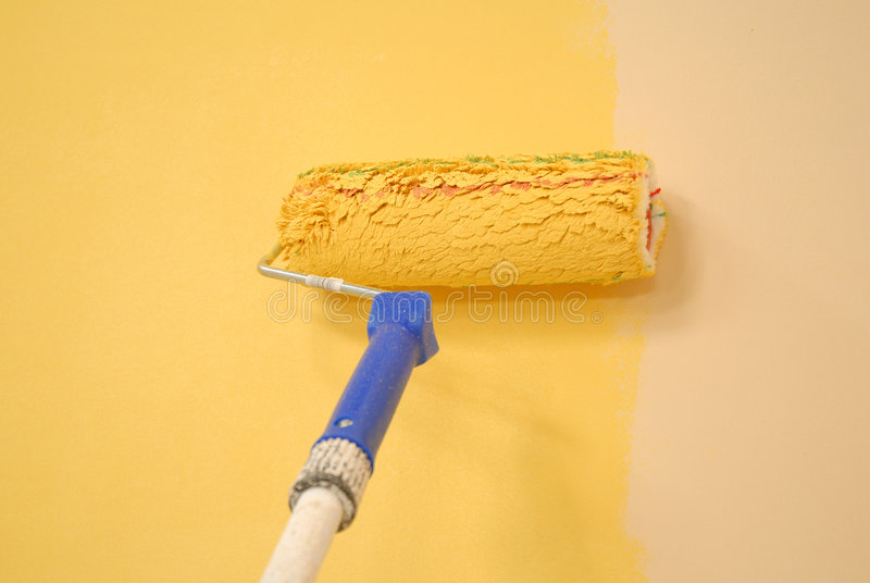 Yellow wall painting roller royalty free stock images