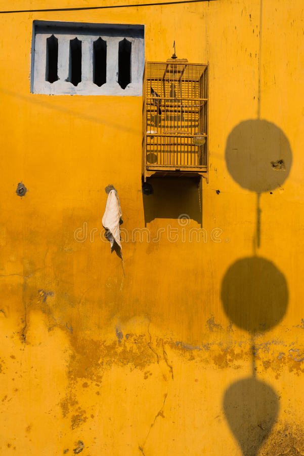 Yellow wall with small windows and bird cages. Hoi An, Vietnam stock photography