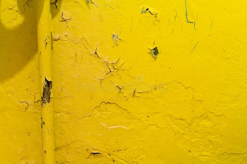 Yellow warm heating on the background of peeling paint on the wall royalty free stock photography