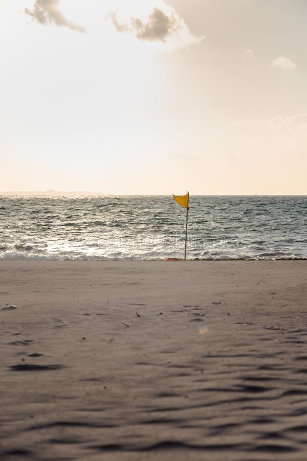 A yellow warning flag indicating adverse conditions on a tropical white sand beach. A yellow warning flag indicating adverse conditions on a tropical white sand stock image