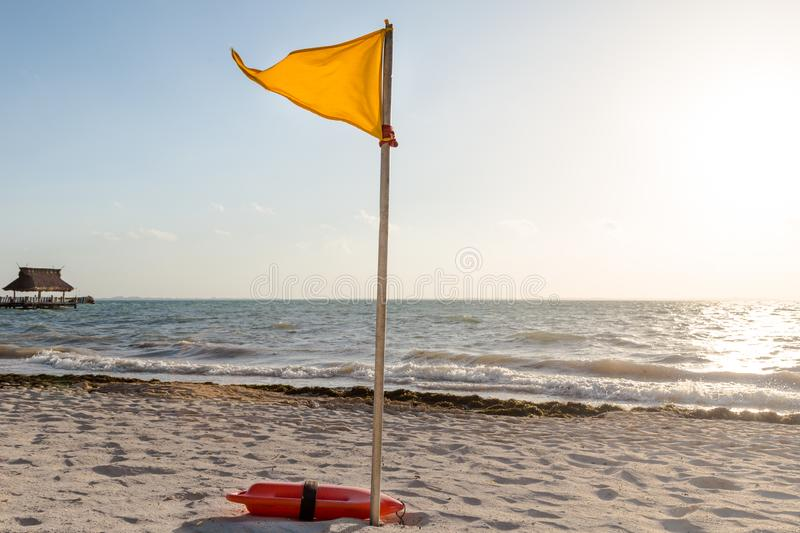A yellow warning flag indicating adverse conditions on a tropical white sand beach. A yellow warning flag indicating adverse conditions on a tropical white sand royalty free stock image