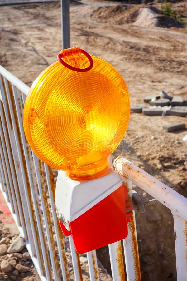 Yellow warning light on fence. On the road royalty free stock images