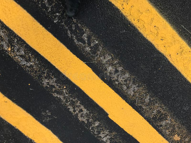 Yellow warning lines on pavement in a parking lot. Grunge effect with old white lines still visible royalty free stock photography