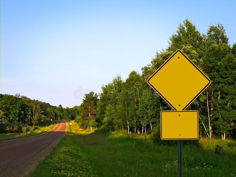 Yellow Warning Road Signs rural roadside in Minnesota at dusk. Yellow Warning Road Signs on gravel rural country roadside at dusk - ADD YOUR TEXT stock photo
