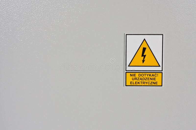 Yellow warning sign triangle with lightning and inscription plate on the electrical cabinet in Polish language. royalty free stock photos
