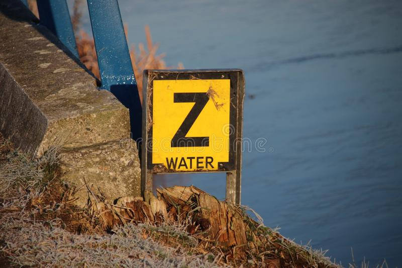 Yellow warning sign with letter `Z ` to warn that a water pipe have sunken on the bottom of the canal. royalty free stock image