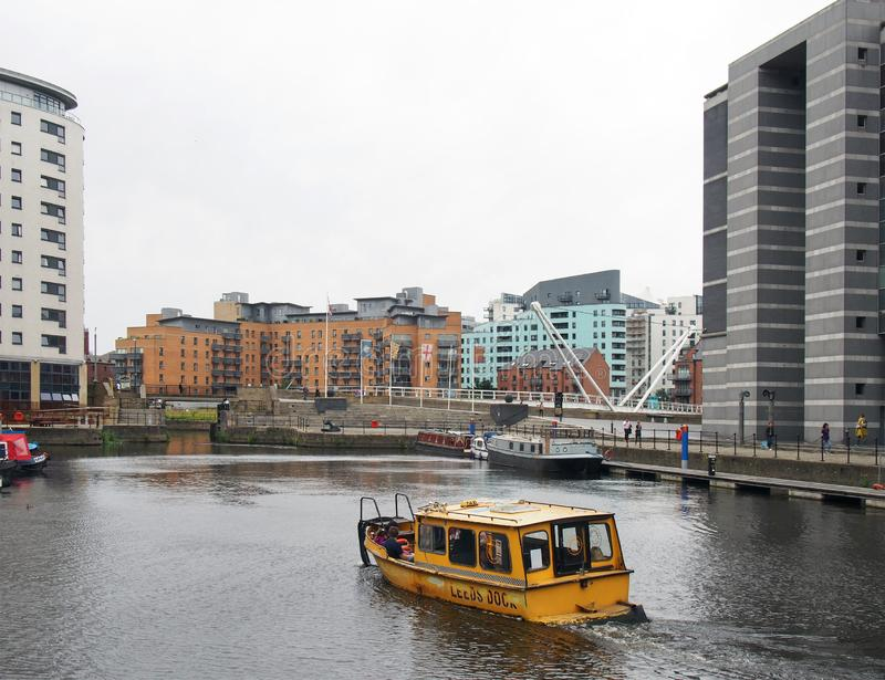 Yellow water taxi leaving leeds dock surrounded by waterside buildings royalty free stock photography