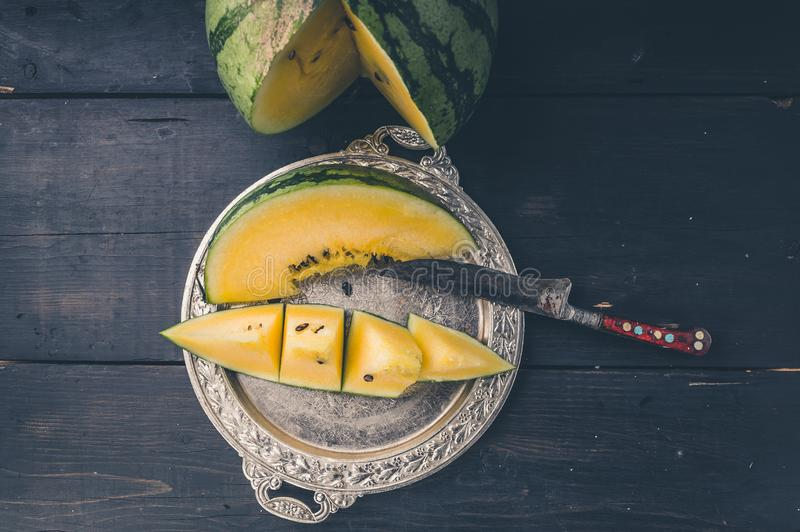Yellow watermelon, slice of watermelon on a silver plate and knife on a dark wooden background. Top view royalty free stock photo