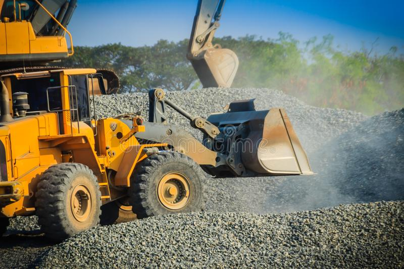 Yellow wheel loader bulldozer is working in quarry against the background of crushed stone storage. stock images