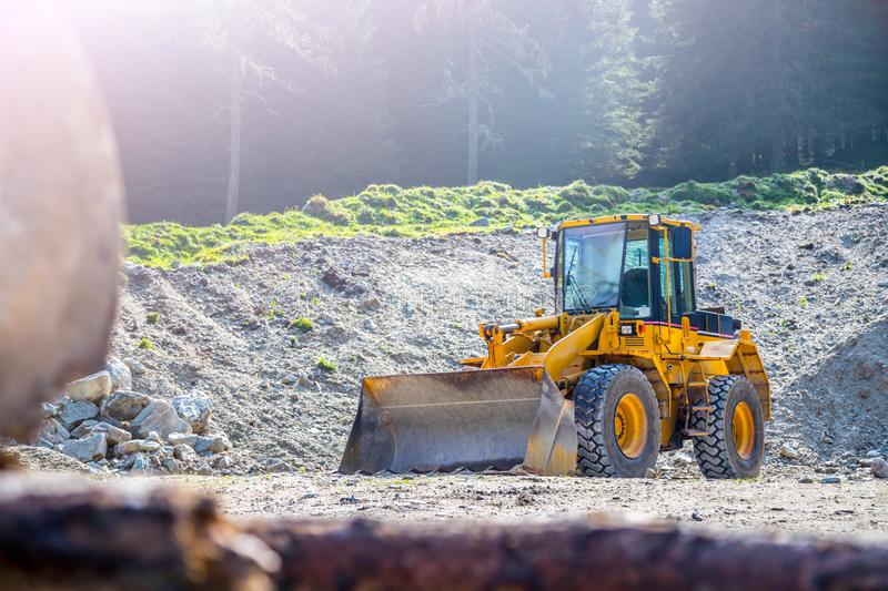 Yellow wheel loader excavator in a quarry. Wheel loader excavator is parking in a quarry, industry, loading, shovelling, construction, land, gravel, heavy royalty free stock photo