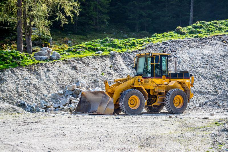 Yellow wheel loader excavator in a quarry. Wheel loader excavator is parking in a quarry, industry, loading, shovelling, construction, land, gravel, heavy royalty free stock image