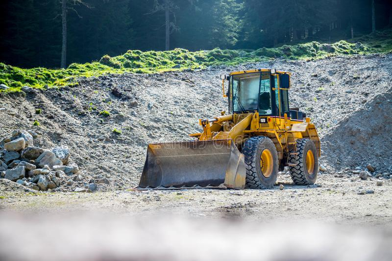 Yellow wheel loader excavator in a quarry. Wheel loader excavator is parking in a quarry, industry, loading, shovelling, construction, land, gravel, heavy stock photos