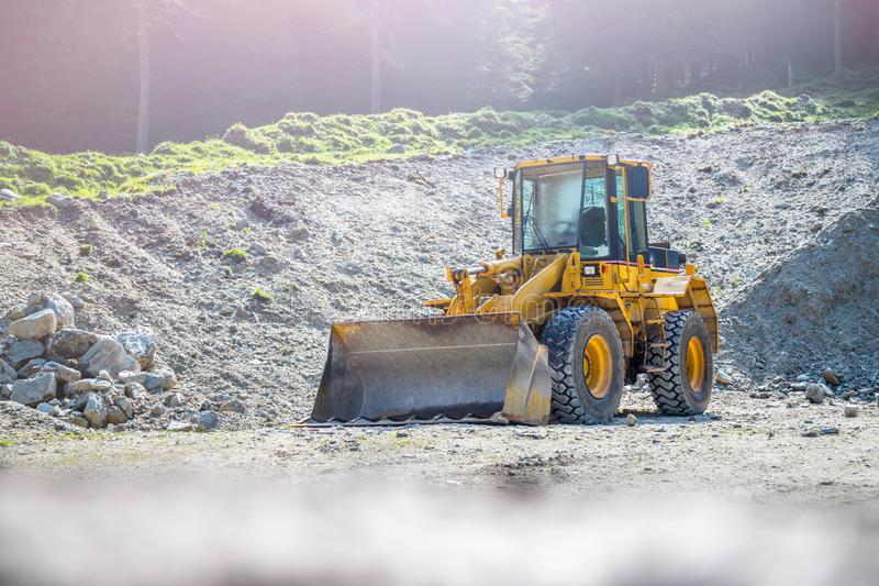Yellow wheel loader excavator in a quarry. Wheel loader excavator is parking in a quarry, industry, loading, shovelling, construction, land, gravel, heavy royalty free stock images