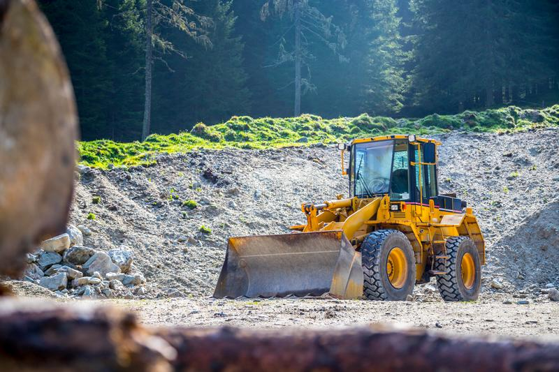 Yellow wheel loader excavator in a quarry. Wheel loader excavator is parking in a quarry, industry, loading, shovelling, construction, land, gravel, heavy stock photography