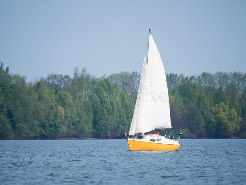 Yellow and white boat sailing on a lake on a sunny day royalty free stock photography